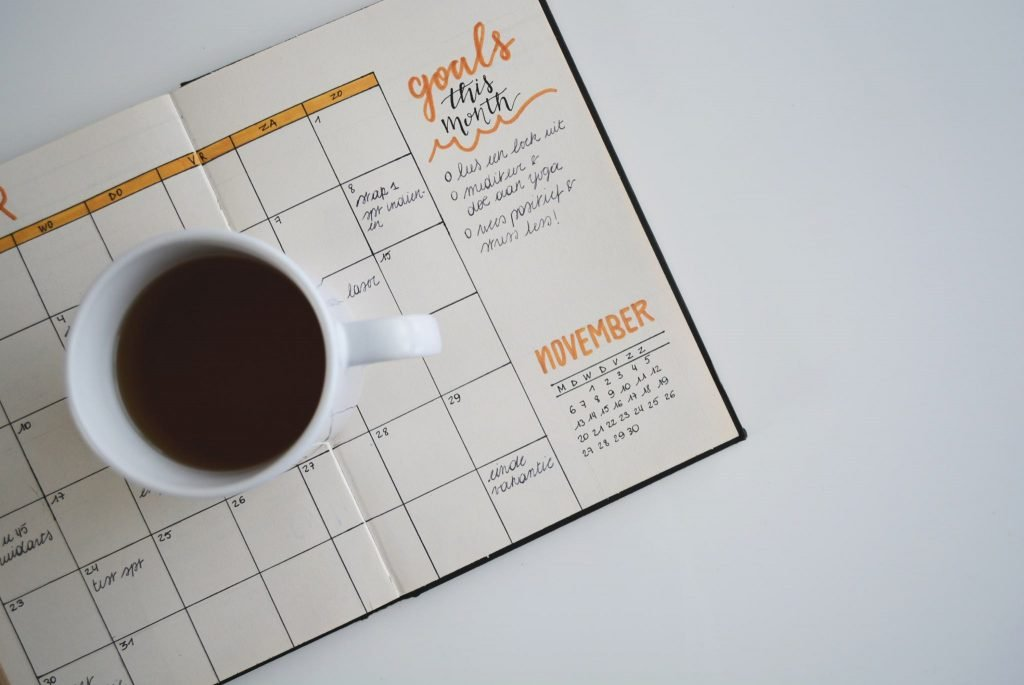 A diary on a desk showing set goals for the month