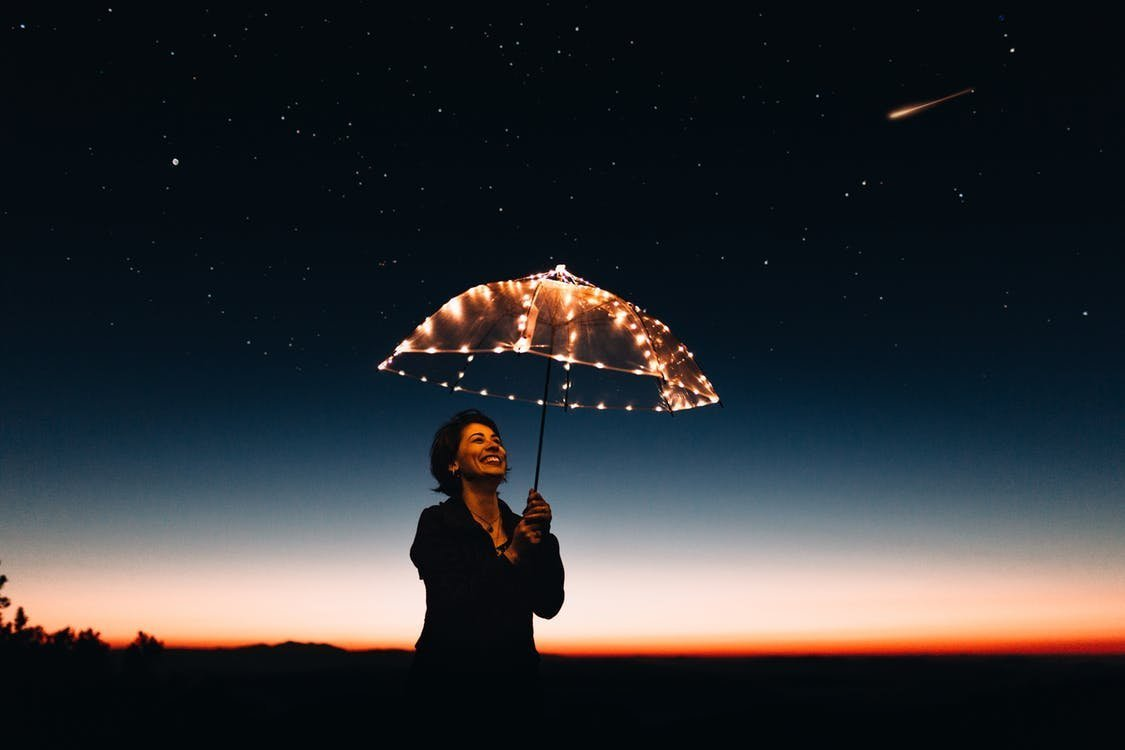 Happy woman holding an umbrella how to be at your best, always!