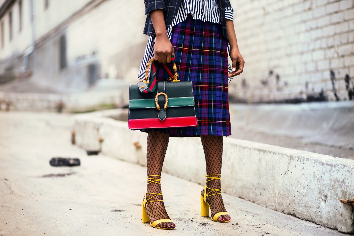 Stylish woman wearing plaid skirt, fishnet and yellow mules